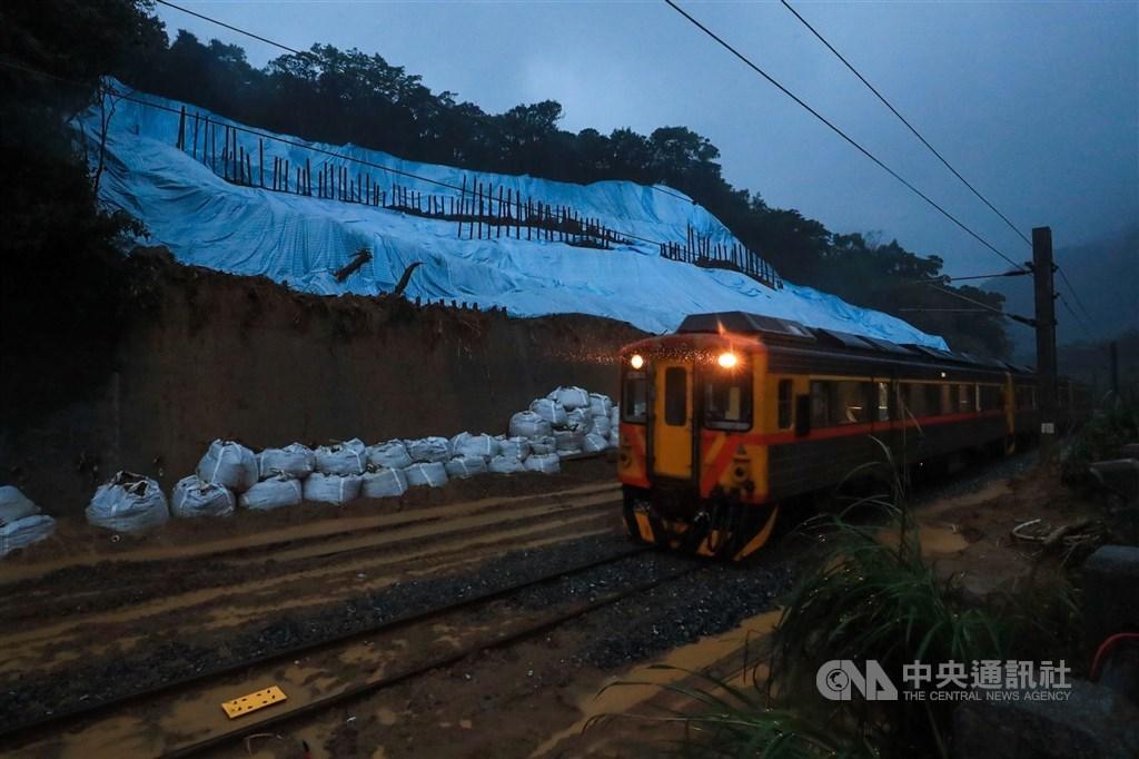 台鐵瑞芳-猴硐路段的邊坡4日嚴重崩塌造成東部路線中斷,13日搶通東正線,圖為14日清晨復駛後列車行經邊坡崩落處。 中央社記者吳家昇攝 109年12月14日