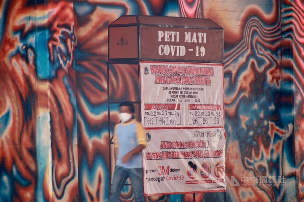 印尼政府防疫小組的數據顯示,境內15日通報新增1萬2818起武漢肺炎確診病例,創下單日新高紀錄。圖為印尼政府防疫團隊在雅加達街頭擺出棺材,提醒民眾不要輕忽防疫的重要性。(中央社檔案照片)