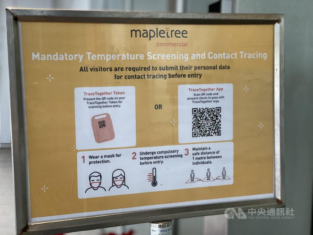 新加坡政府研發追蹤接觸者的「合力追蹤」手機應用程式及防疫器,民眾進入公共場所前須先掃描。圖為PSA大樓入口處的提醒標示。中央社記者侯姿瑩新加坡攝 110年1月6日