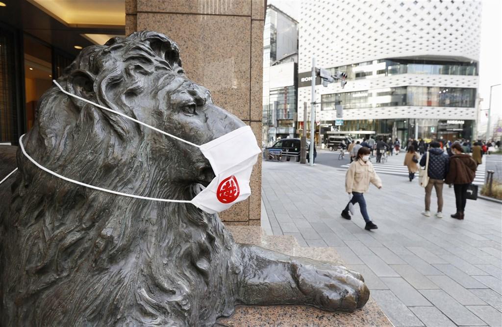 日本7日針對武漢肺炎疫情二度發布「緊急事態宣言」。這次宣言適用範圍較上次縮小許多,限制措施也相對「有限」。圖為7日日本橋三越本店主入口獅子雕像被戴上口罩。(共同社)