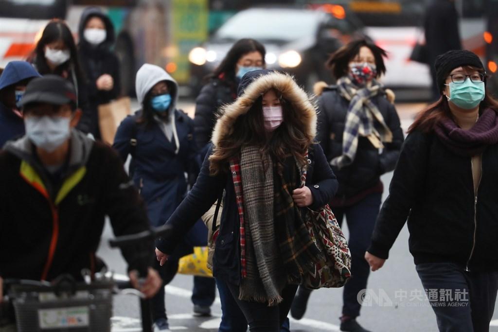 受寒流持續影響,12日各地寒冷,民眾走在街頭穿上厚外套、戴上帽子禦寒。中央社記者王騰毅攝 110年1月12日