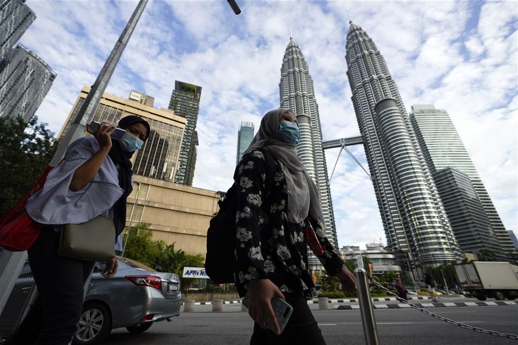 馬來西亞國家元首蘇丹阿布都拉12日宣布大馬全國進入緊急狀態,以遏止2019冠狀病毒疾病疫情擴散。圖為民眾戴口罩經過吉隆坡雙峰塔前。(美聯社)