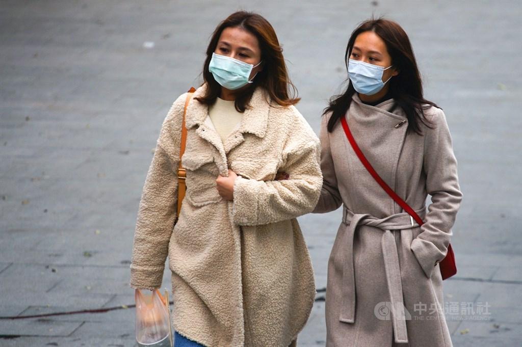中央氣象局表示,17日受強烈大陸冷氣團影響,北部及東北部一整天濕冷,全台18縣市可能有攝氏10度以下低溫,外出民眾穿起大衣保暖。中央社記者王騰毅攝 110年1月17日