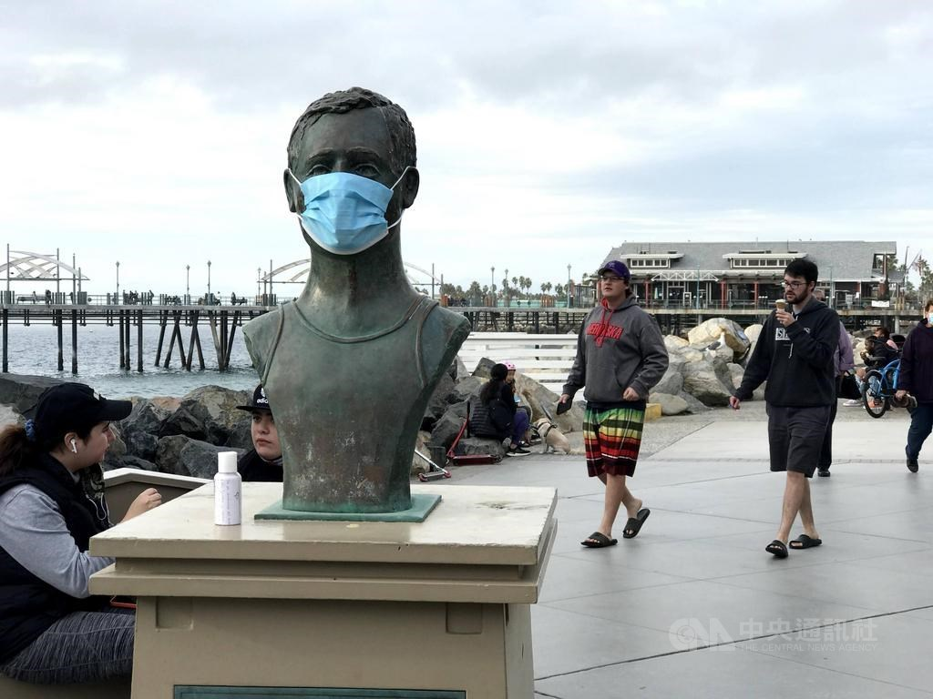 根據約翰霍普金斯大學和冠狀病毒疾病追蹤計畫統計數據,加州成為全美首個確診數突破300萬大關的州。圖為加州芮當多海灘傳奇救生員佛利斯雕像被戴上口罩,與周圍不戴口罩的遊客形成對比。(中央社檔案照片)