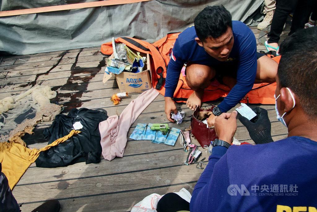 印尼三佛齊航空的一架班機9日墜海,機上有62人,至今確認43人的身分。圖為搜救人員檢視搜尋到的旅客身分證。圖攝於12日。中央社記者石秀娟雅加達攝 110年1月21日