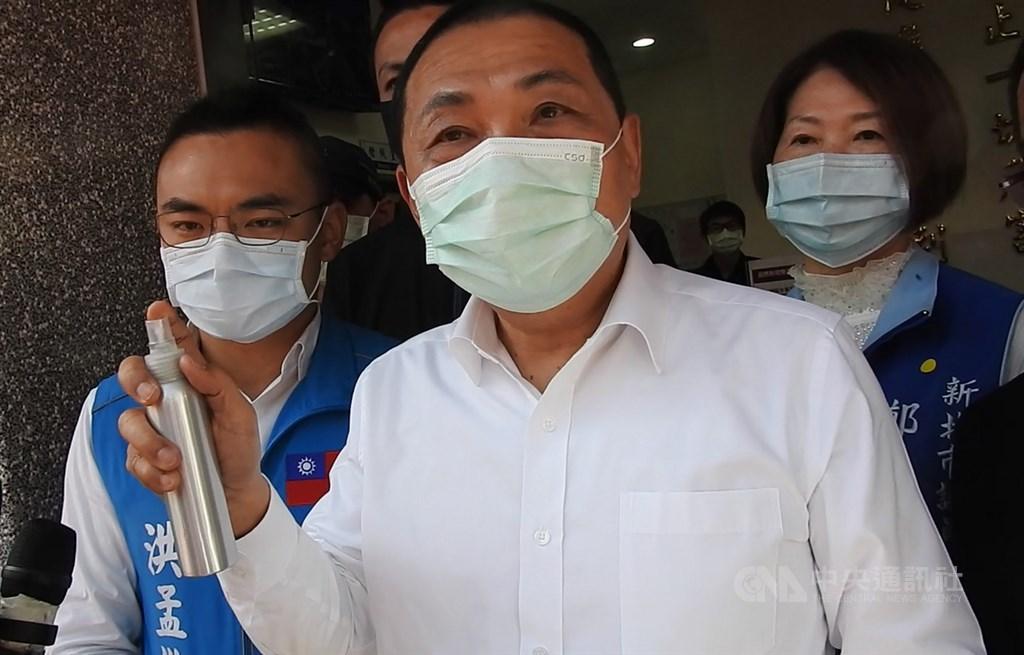 新北市長侯友宜(中)21日受訪時表示,現階段防疫不是只有戴口罩,更重要的是手部清潔,所以也要求員警隨身帶酒精噴消液,隨時把手部消毒做到位。中央社記者王鴻國攝 110年1月21日