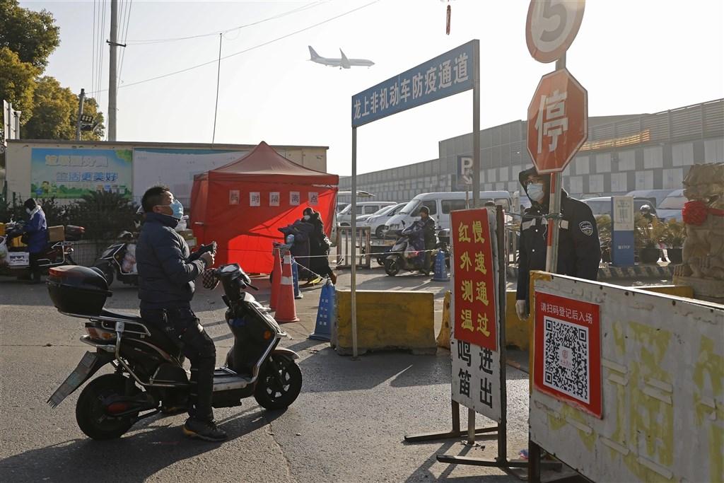 上海21日新增3例武漢肺炎確診病例,一處居民區列為中風險地區,且居民將集中至賓館隔離;主動篩查出病例的兩家醫院已暫停門診。圖為上海民眾進市場前,通過防疫通道。(中新社)