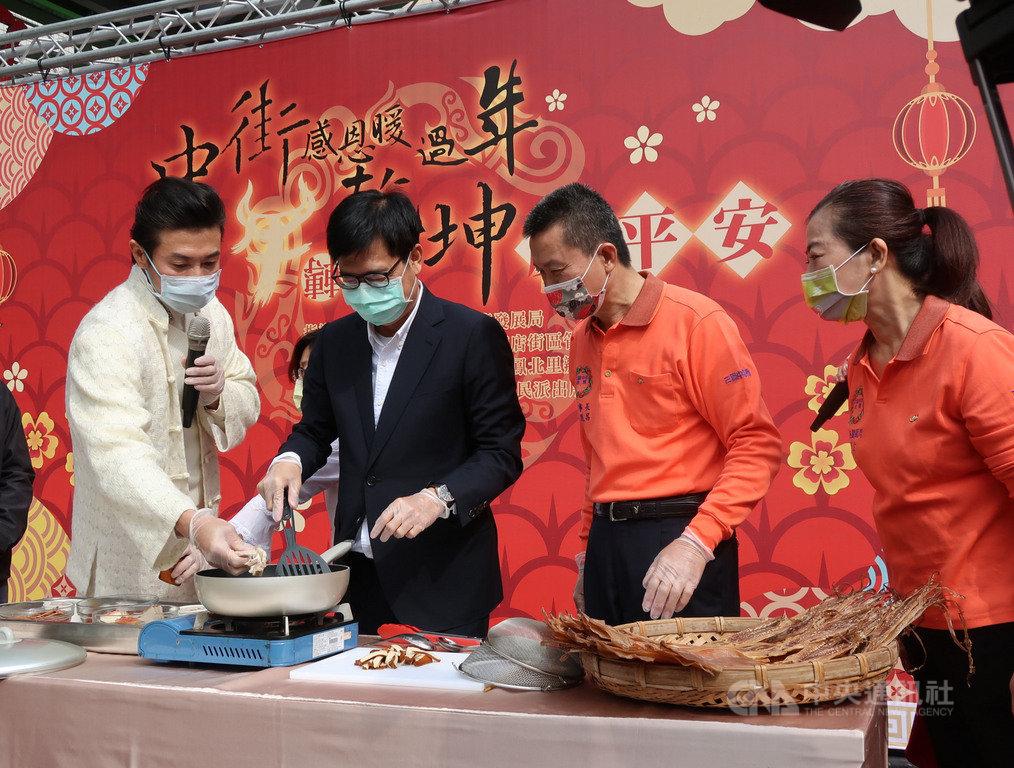 高雄市長陳其邁(左2)24日到三鳳中街行銷年貨大街商品,並與名廚陳鴻(左1)一起示範做年菜,介紹健康「防疫年菜」。中央社記者王淑芬攝  110年1月24日
