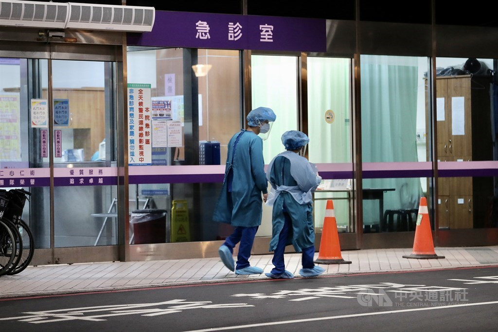 疫情指揮中心24日宣布,台灣增2例本土個案,為桃園醫院群聚衍生,為出院病患及其同住家人。圖為桃醫周邊身著防護衣的工作人員走動。(中央社檔案照片)