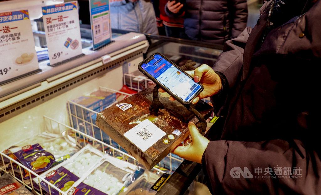 中國防疫專家張文宏24日說,目前沒有發現因為食用進口冷鏈食品而感染武漢肺炎的病例,「這個概率已經接近於比空難都低的時候」。圖為湖北武漢市一間超市,消費者用手機掃碼查看一盒進口冷凍鮮蝦的檢測資訊。(中新社提供)中央社 110年1月25日