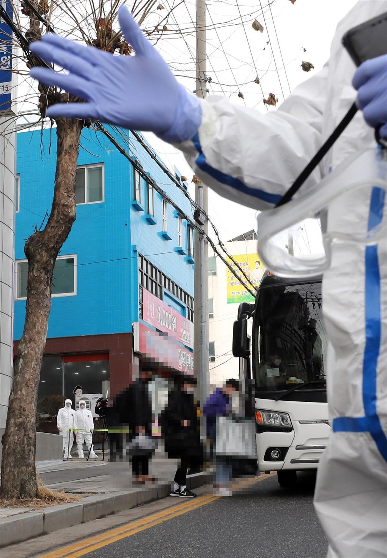 韓國大田市一所宗教教育機構爆出2019冠狀病毒疾病群聚感染事件,至少127人確診。圖為機構學生陸續上公車,被送往鄰近的治療中心。(韓聯社)