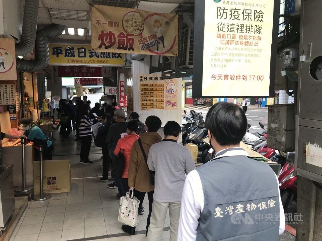 台灣產物保險公司防疫保單25日下午5時截止收件,台北市館前路的台產總公司外湧現排隊民眾,希望購買保單,工作人員在南陽路的隊伍末端舉牌。中央社記者徐肇昌攝 110年1月25日