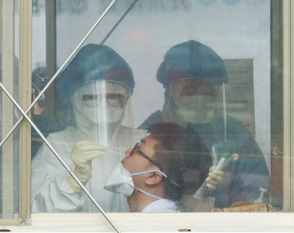 桃園醫院武漢肺炎群聚案擴大,桃醫專案已由中央跟地方政府全面啟動,追溯、隔離機制目前運作順利。圖為26日桃園醫院戶外採檢區,醫護人員為院內醫師進行採檢。中央社記者施宗暉攝 110年1月26日