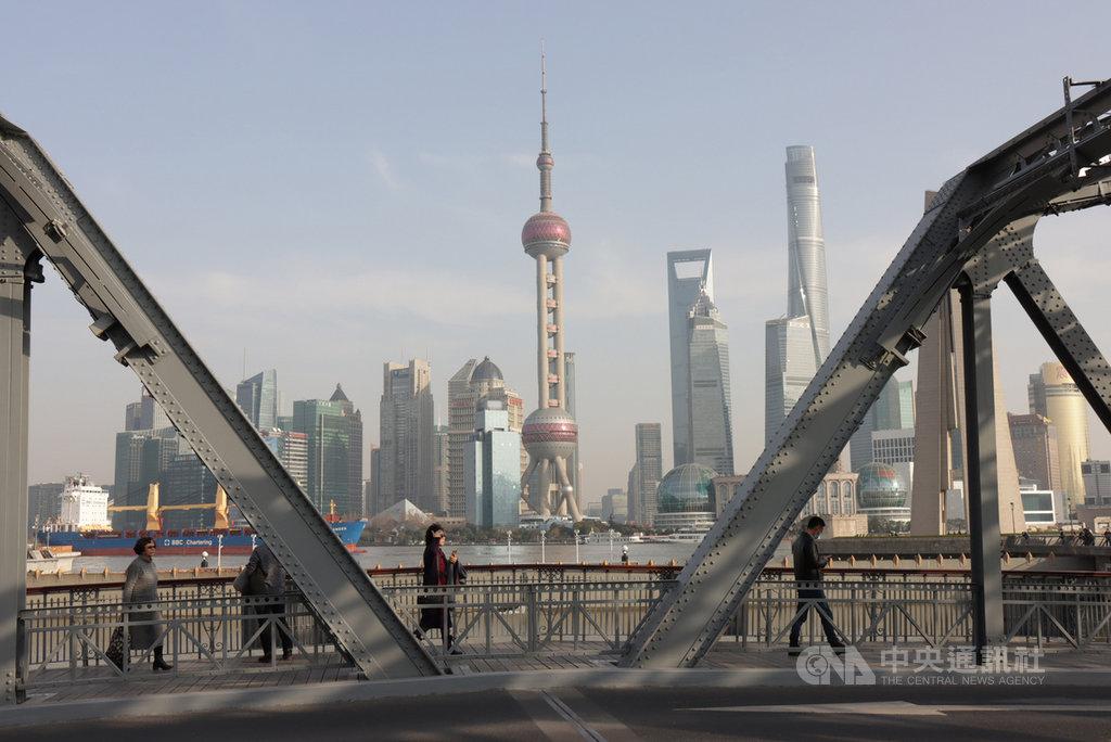 在上海生活與工作的人們匆匆走過外白渡橋,背景是象徵繁榮發展的陸家嘴金融區。中央社記者張淑伶上海攝 110年1月27日