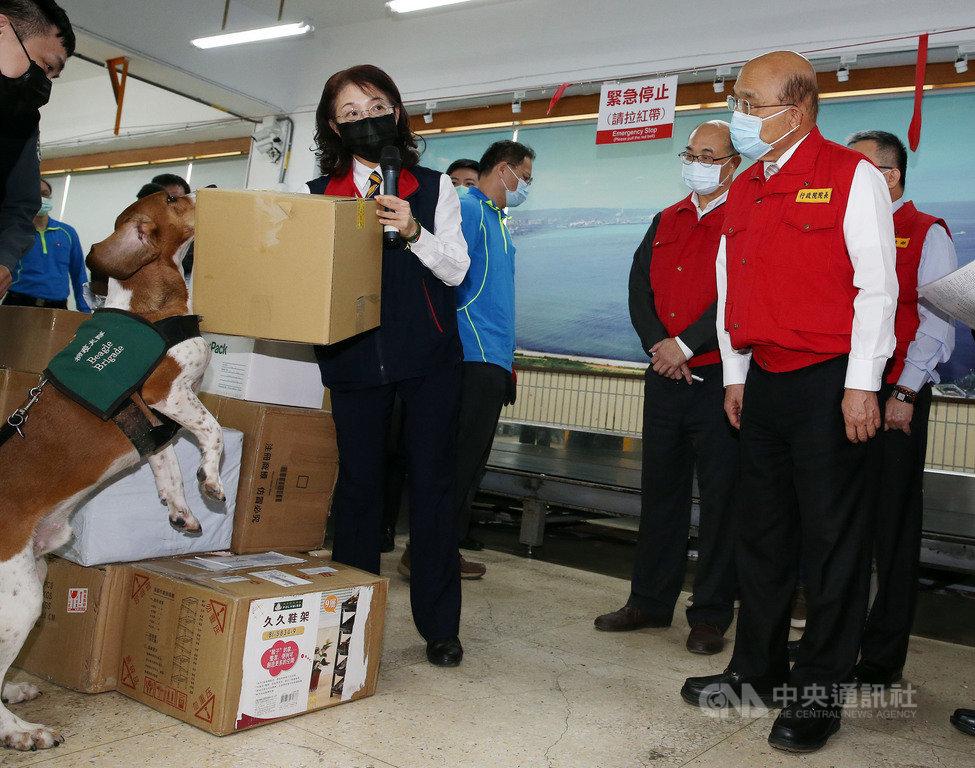 春節將至,行政院長蘇貞昌(右)27日上午前往台北郵件處理中心,視察春節國際郵包檢疫流程,檢疫犬現場進行嗅聞作業,阻絕疫情入侵。中央社記者郭日曉攝 110年1月27日
