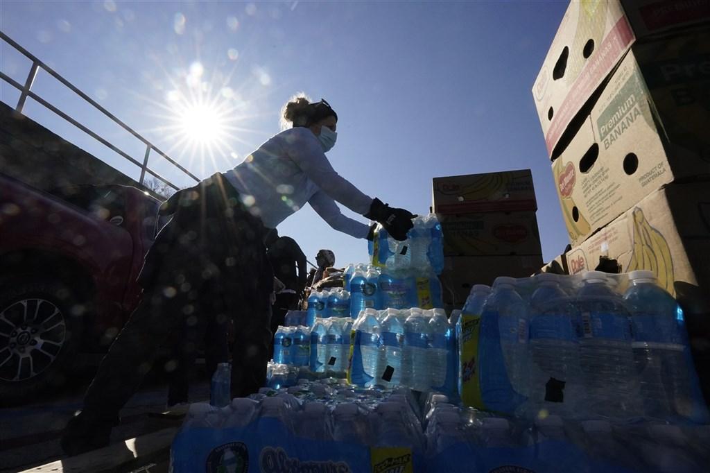 德州遭受強烈暴風雪襲擊,經歷數天破紀錄低溫後,雖全州電力已近恢復,但仍有約1430萬人缺乏乾淨飲水。圖為19日食物銀行志工發放瓶裝水給民眾。(美聯社)