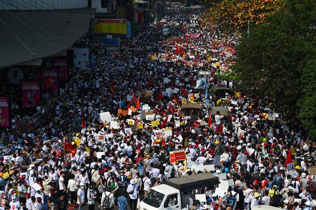 緬甸民眾22日發起22222全國大罷工,許多店家拉下鐵門不做生意,上萬民眾無懼軍方威嚇持續走上街頭,成為政變至今規模最大的街頭抗爭。圖為示威者在仰光街頭抗議。(法新社)