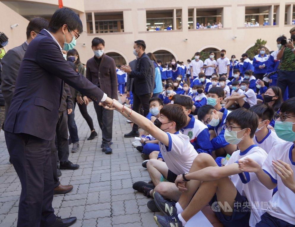全國中小學22日開學,高雄市長陳其邁(前左)到三民區三民高中關心開學防疫工作,與學生擊拳互動,受到學生們熱烈歡迎。中央社記者董俊志攝 110年2月22日