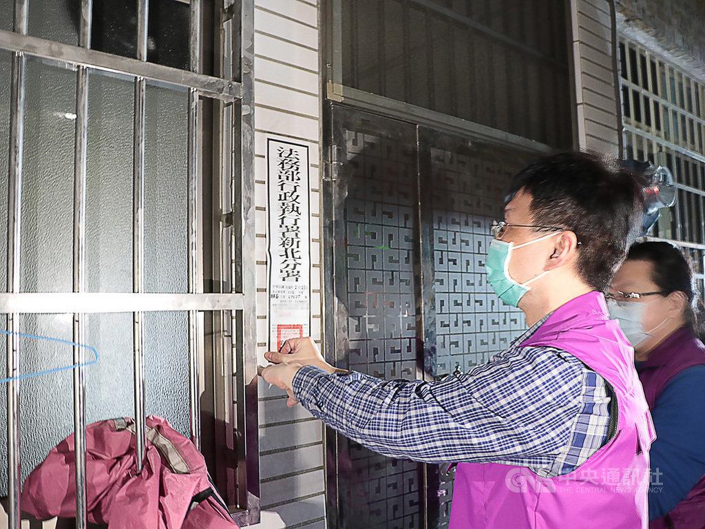 法務部行政執行署新北分署23日兵分三路,展開「強力執行滯欠防疫案件罰鍰專案」,新北分署人員在欠繳罰鍰義務人名下建物張貼封條。(行政執行署新北分署提供)中央社記者沈佩瑤傳真  110年2月23日