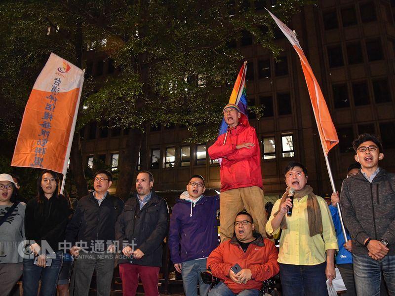 同志運動先驅祁家威(紅衣者)與台灣伴侶權益推動聯盟等民團成員17日晚間到中選會前,抗議中選會通過反同公投提案,高呼「人權豈能公投」。中央社記者王飛華攝 107年4月17日