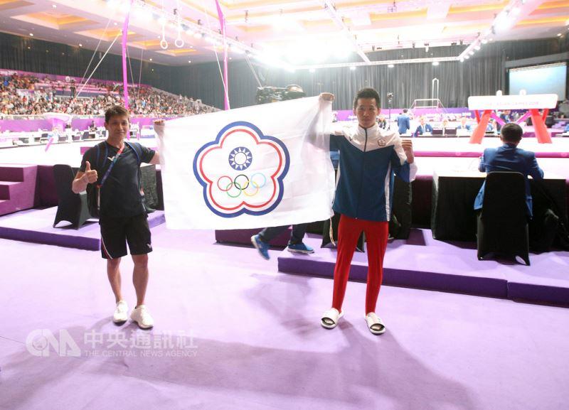 2018雅加達亞運中華體操隊好手李智凱(前右)23日在體操單項決賽男子鞍馬項目勇奪金牌,賽後與教練林育信(左)在場邊開心高舉中華奧會會旗留影。中央社記者張新偉攝 107年8月23日