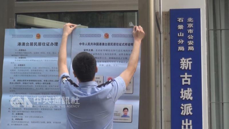 陸委會擬修正兩岸人民關係條例,對「港澳台居民居住證」採登記制。圖為北京市西郊的石景山區新古城派出所,員警在門口張貼公告及居住證樣式。(中央社檔案照片)