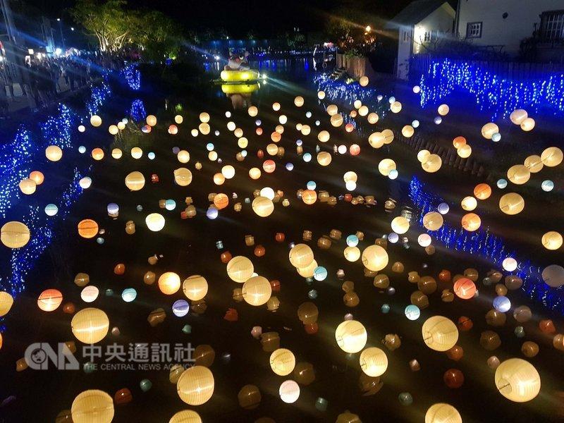 農曆過年期間,不少民眾造訪台南鹽水的「月津港燈節」,其中一件作品「行星計畫」,將大大小小的燈籠吊掛在河面上,夜晚時配合燈光投射、倒影映照,優美的畫面成為不少民眾拍照、打卡熱點。中央社記者鄭景雯攝 108年2月18日