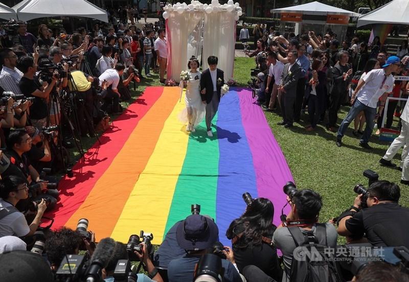 同婚登記24日開跑,同婚團體婚姻平權大平台在戶外舉辦「幸褔起跑線Wedding Party」,同志新人以彩虹旗當作紅毯步入會場,吸引大批媒體到場拍攝。中央社記者裴禛攝 108年5月24日