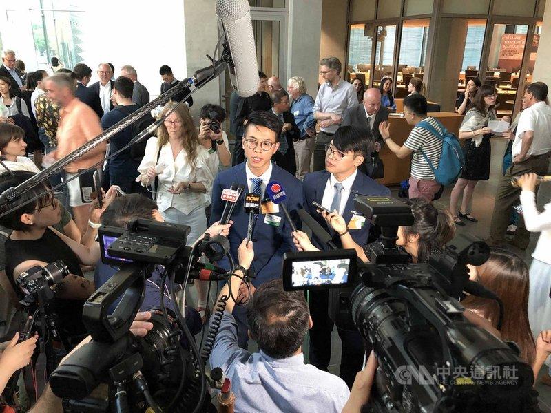 獲德國政治庇護的香港本土派人士黃台仰(前右2)和李東昇(前右1)4日在德國國會演講,吸引大批香港記者採訪。中央社記者林育立柏林攝 108年6月5日