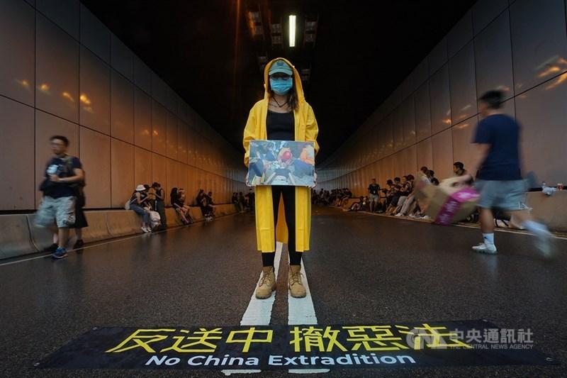 香港立法會議員17日率反修訂逃犯條例群眾至行政長官辦公室外,群眾順勢占據龍和道,一名示威者站在隧道口表訴求。中央社記者裴禛香港攝 108年6月17日