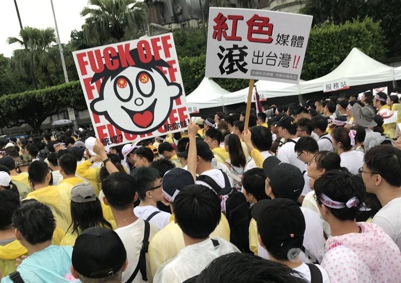 「拒絕紅色媒體、守護台灣民主」活動23日下午在總統府前凱達格蘭大道登場,參與民眾高舉反親中媒體的自創標語,表達訴求。中央社記者徐肇昌攝 108年6月23日