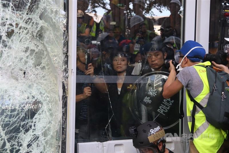 香港大批反修訂逃犯條例示威者1日衝擊立法會大樓,防暴警察在議會內戒備,但保持克制,並未衝出驅散群眾。 中央社記者張謙香港攝 108年7月1日