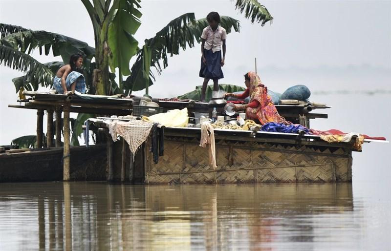雨季豪雨連日狂炸印度、尼泊爾、孟加拉和巴基斯坦,印度東北部的阿薩姆省受洪水侵襲,民眾逃到住家屋頂。(檔案照片/法新社提供)