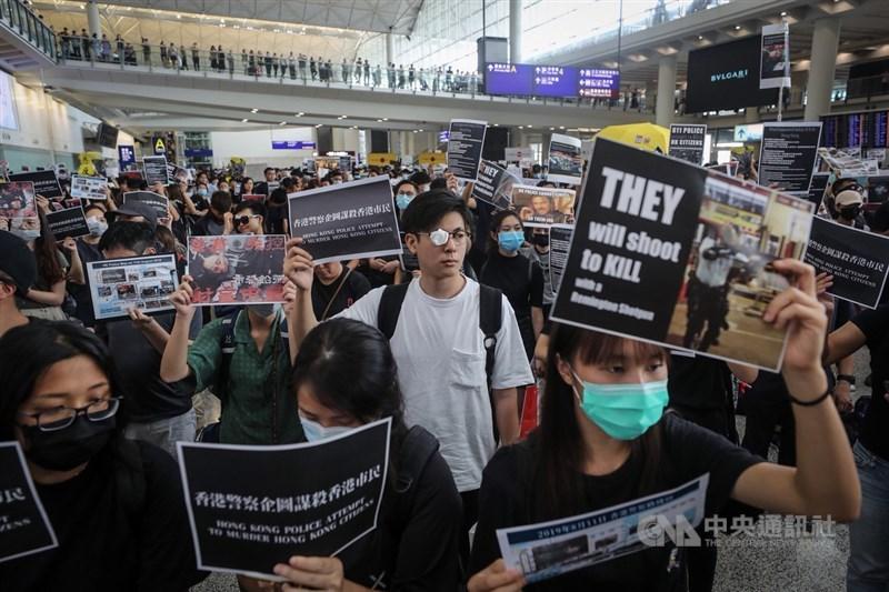 一名「反送中」示威女子11日眼部受傷,外界質疑是被港警布袋彈所傷。圖為12日示威者齊聚香港國際機場要求港警「以眼還眼」。(中央社檔案照片)
