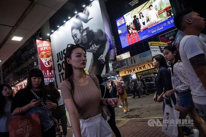 香港眾志秘書長黃之鋒和成員周庭30日上午遭逮捕,法院裁判官同意各以港幣1萬元現金交保外出,但要遵守宵禁令等。傍晚旺角街頭電視牆播放著相關新聞,但並未吸引太多街頭民眾的目光。中央社記者吳家昇攝 108年8月30日