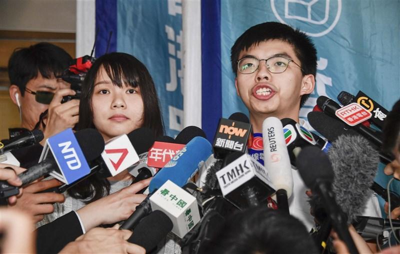 香港眾志祕書長黃之鋒(右)和成員周庭30日上午突然被捕,下午交保。(共同社提供)