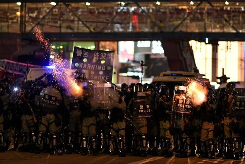 香港當局宣布5日零時起禁止蒙面示威後,4日晚間多處出現「反送中」黑衣示威者,警方晚間10時左右,在銅鑼灣施放催淚彈驅散民眾。(法新社提供)