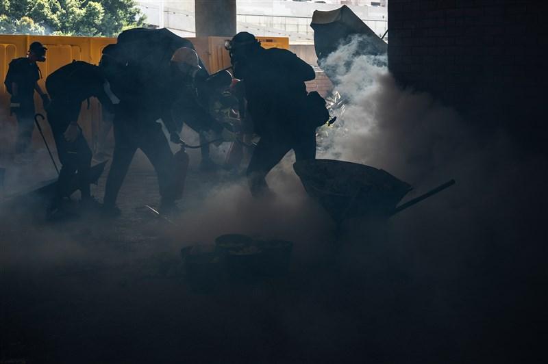 香港數間大學的校園近來成為反送中抗議者和警方衝突的戰場。圖為11日理工大學學生在警方施放催淚彈後,使用滅火器撲滅。(法新社提供)