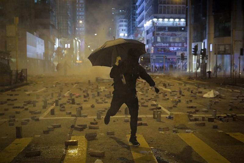 香港「三罷」運動在入夜後,示威者轉回中環、旺角、銅鑼灣與西灣河等地,在街道築起路障、焚燒雜物與噴寫抗議標語。圖為一名示威者逃離港警發射的催淚彈。(美聯社)