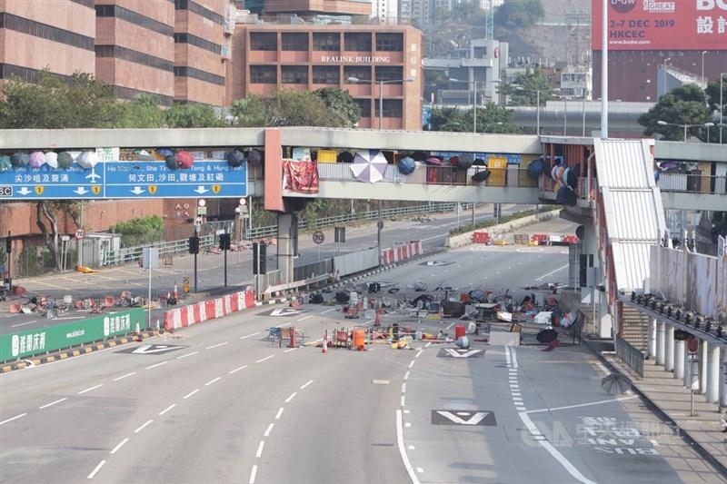 示威者從橋上向海底隧道路面投下雜物,令道路阻塞。圖為示威者站在連接理工大學的橋上,用雨傘遮擋自己。中央社記者張謙香港攝 108年11月14日