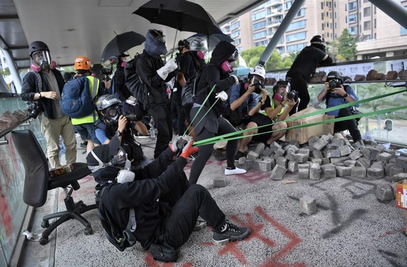 圖為反送中示威者12日上午集結於香港歌和老街近城市大學學生宿舍一段,以大型彈弓向警員發射石塊並丟擲汽油彈。(中通社提供)中央社