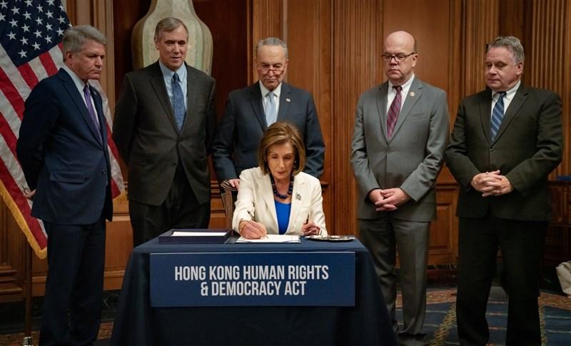 美國眾議院議長裴洛西(前)21日在跨黨派議員見證下,將「香港人權與民主法案」送出國會並遞交川普總統簽署。(圖取自twitter.com/SpeakerPelosi)