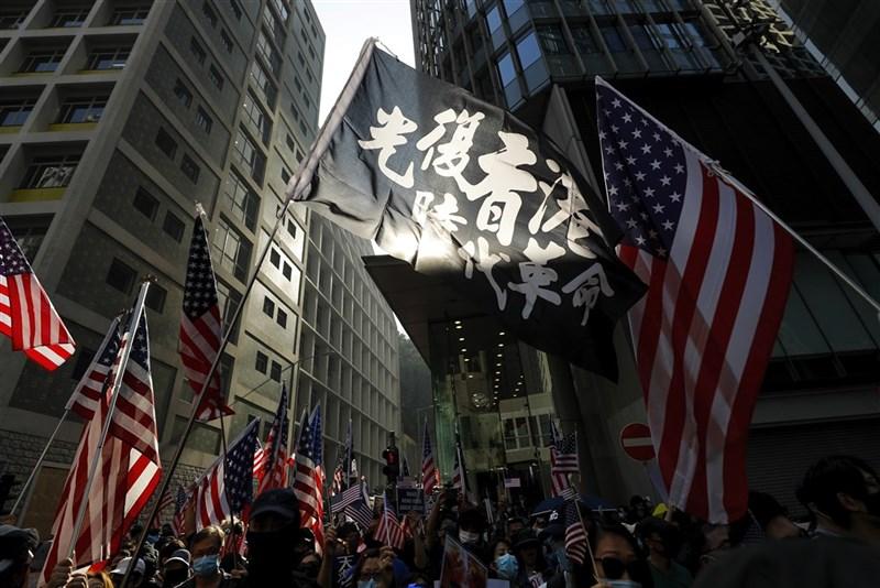 中國控訴美國5個非政府組織支持「反中亂港分子」,並對其實施制裁。美國國務院2日強硬回應,批評中國指控不實。圖為香港民眾1日遊行揮舞「光復香港」旗幟及美國國旗。(美聯社)