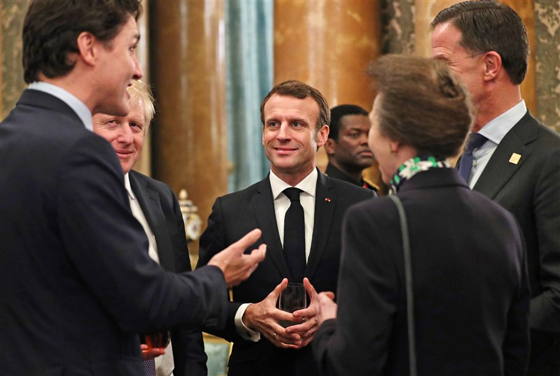 加拿大總理杜魯道(左)、英國首相強生(左2)和法國總統馬克宏(左3)等人4日被拍到在白金漢宮一場晚宴中,疑似調侃美國總統川普記者會花太久時間。(法新社提供)