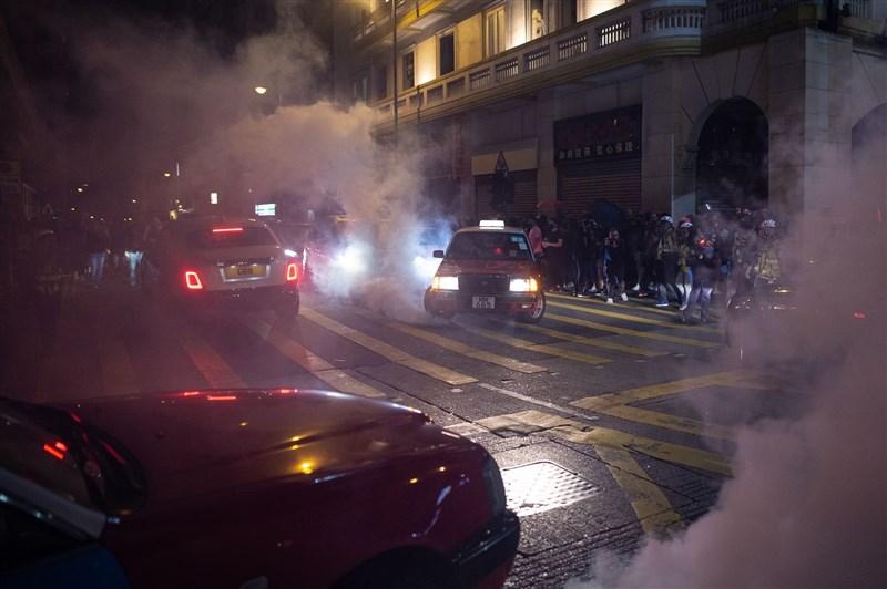 在耶誕平安夜,香港多處仍有「反送中」示威者聚集,防暴警察予以驅散。(法新社提供)