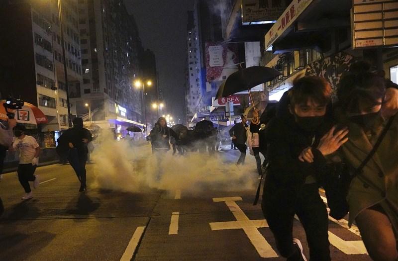 香港各區市民跨年夜聚集悼念「8.31」港警無差別車廂襲擊乘客事件,港警1日凌晨0時07分發射催淚彈驅散人群。(美聯社)
