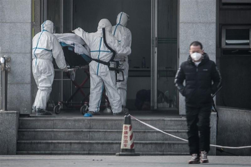 2019新型冠狀病毒肺炎疫情在中國持續蔓延,已經擴散至北京、深圳、上海等地。圖為醫護人員將患者送入前往專門收治武漢肺炎的金銀潭醫院。(法新社提供)