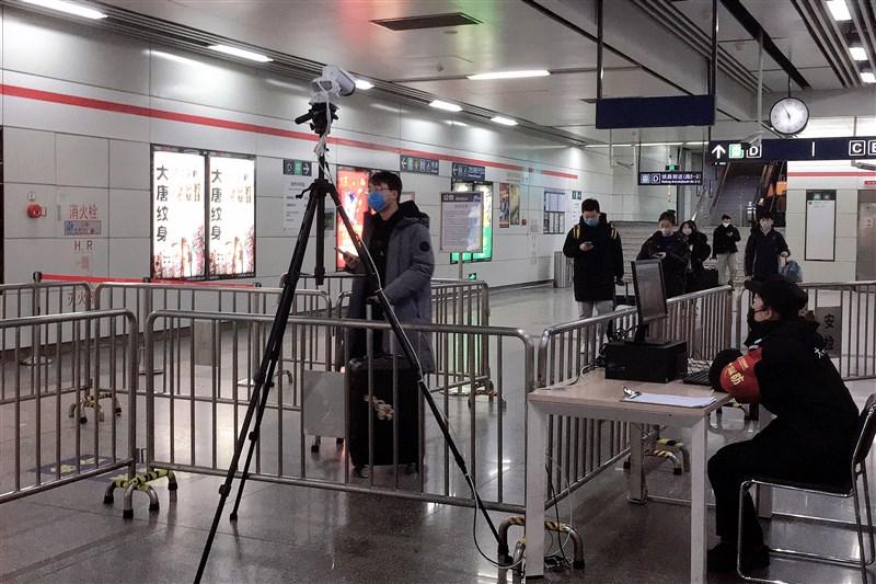 杭州市人民政府4日凌晨發布通告,全市所有村莊、小區、單位實行封閉式管理,人員進出一律測量體溫,並出示有效證件。圖為杭州東站地鐵站入口,工作人員通過紅外熱成像儀檢測乘客體溫。(中新社提供)