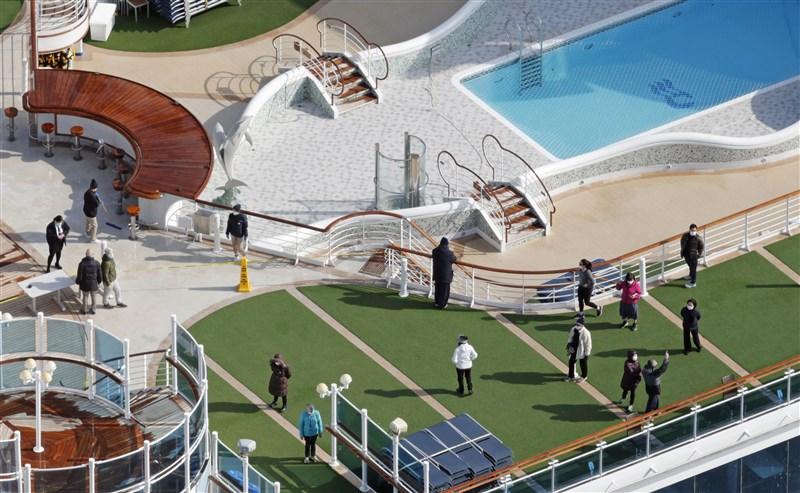 受武漢肺炎疫情殃及而停泊日本橫濱港外隔離的鑽石公主號遊輪,逾130人確診染病,且船組員染病增多。圖為鑽石公主號乘客7日在甲板散步。(共同社提供)