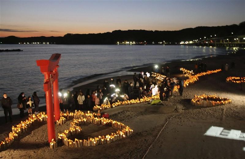 日本第一批從中國包機返鄉的日本人中,有176人被安置在千葉縣勝浦市的飯店觀察,有望從12日起依序返家。勝浦市居民11日晚間在飯店沙灘上投影訊息,為飯店內遭隔離的日人送暖。(共同社提供)